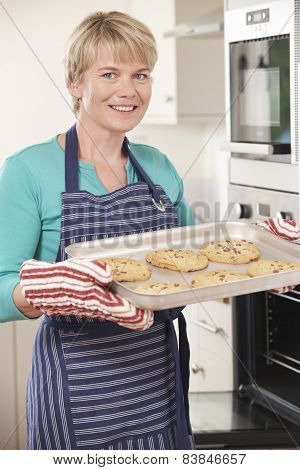 Woman In Kitchen Holding Tray With Home Baked Cookies