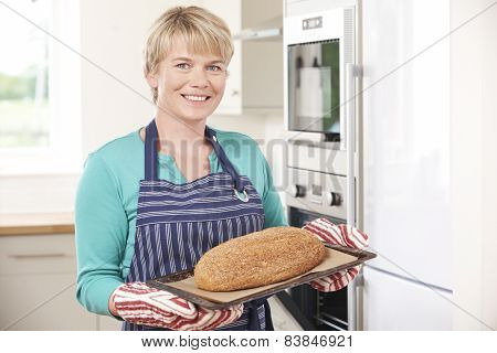 Woman Taking Home Baked Loaf Out Of Oven