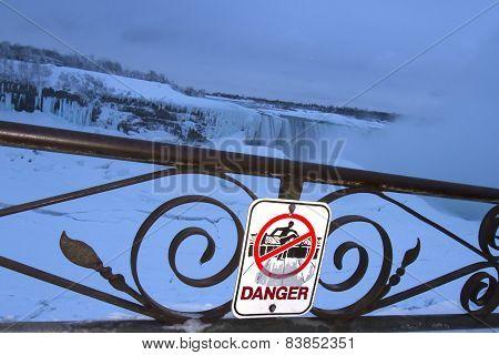 Danger Of Falling Sign With Frozen Niagara Falls