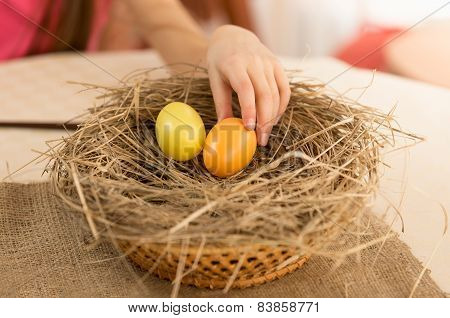 Closeup Shot Of Child Hand Picking Easter Egg From The Nest