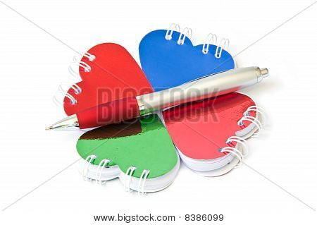 Four heart-shaped notepad and pen.