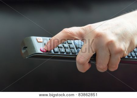 Person using remote control for TV