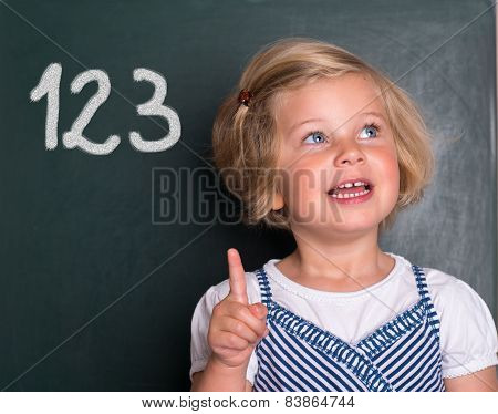 Little Girl In Front Of Black Board With Forefinger Up