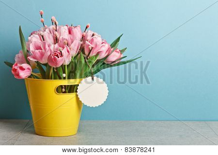 Bouquet Of Pink Fresh Tulips With Pussy-willow In Yellow Bucket On Table On Blue Backround