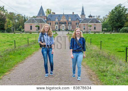 Two girls walking away from castle