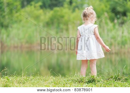 Little Girl In Light Summer Dress Near Forest Pond