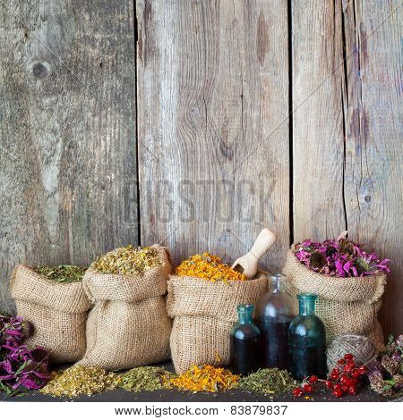 Healing Herbs In Hessian Bags And Blue Bottles With Tincture On Old Wooden Background, Herbal Medici