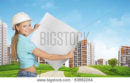 Woman in helmet holds white paper. Looking at camera, smiling. Green hills with road and buildings