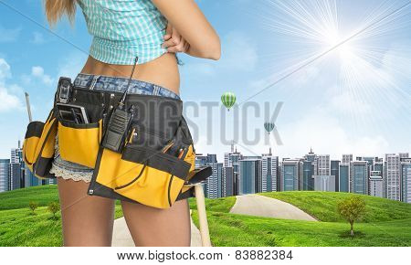 Woman in tool belt stands back. Green hills with road and buildings