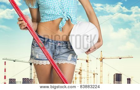 Girl holding spirit level and helmet. Cropped image. City as backdrop