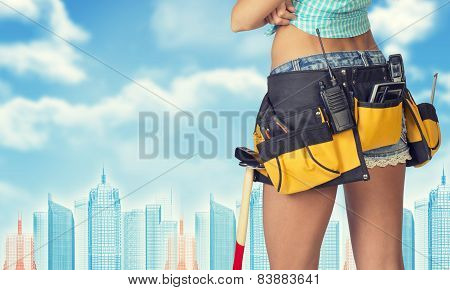 Woman in tool belt stands back, crossed arms. Cropped image. Wire-frame buildings as backdrop