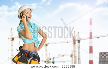 Woman in helmet and tool belt, talking on phone, smiling. Tower cranes as backdrop
