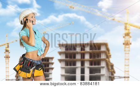 Woman in helmet and tool belt, talking on phone. Construction site as backdrop