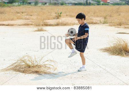 Boy Play Football On The Dry Soil Ground