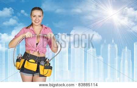 Woman in tool belt connects two flexible hoses. Wire-frame buildings as backdrop