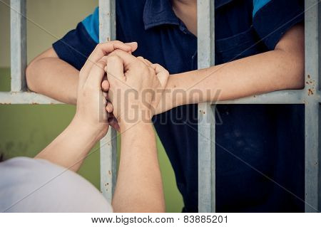 Mom Hand Holding Kid At The Back Of The Iron Bar