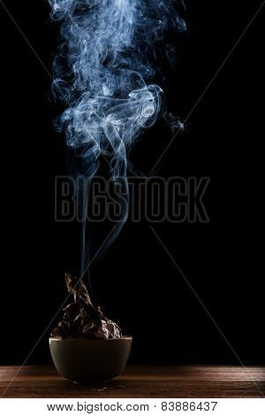 Beautiful Smoke And Lighting Of Paper Burned In Ceramic Bow Against Blackness Background
