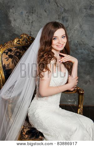 Photo of a beautiful smiling happy bride in luxurious wedding dress into elegant expensive interior