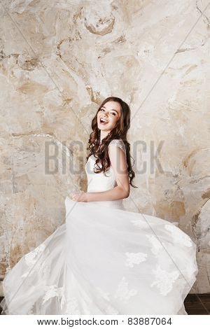 Beautiful happy smiling bride with perfect makeup and hair style in elegant wedding dress