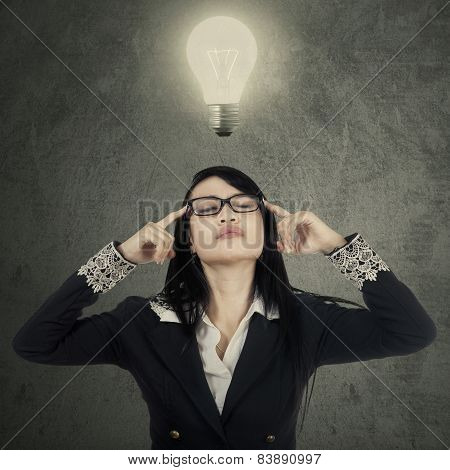 Female Worker Thinking Under Bright Lamp