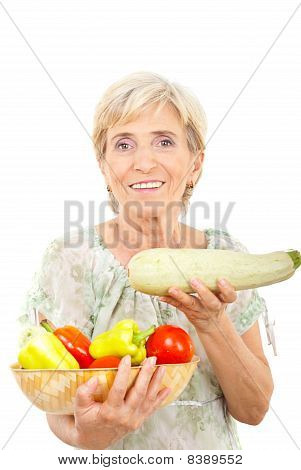 Cheerful Aged Woman Showing Zucchini