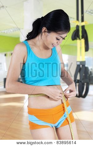 Young Woman Measuring Waistline At Gym