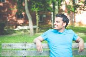 picture of indian blue  - Closeup portrait happy smiling regular young man in blue shirt sitting on wooden bench relaxed looking to side. Retro faded vintage look
