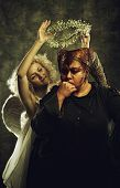 stock photo of hells angels  - Pretty angel holding nimbus under horned head of demon - JPG