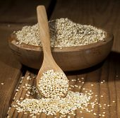 pic of quinoa  - Uncooked quinoa in the wooden bowl and spoon on a wooden background - JPG
