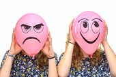 picture of incognito  - Two girls holding pink balloons with drawn facial happy and angry expression - JPG