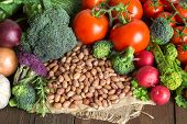 stock photo of pinto  - Pile of pinto beans and vegetables on a wooden bacground - JPG