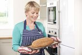 stock photo of home-made bread  - Woman Holding Tray With Home Made Loaf Of Bread - JPG
