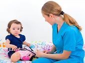 stock photo of babysitter  - Photo of an adorable baby examined by the doctor - JPG