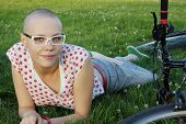 foto of bald head  - bald woman lying on the grass  with bicycle - JPG
