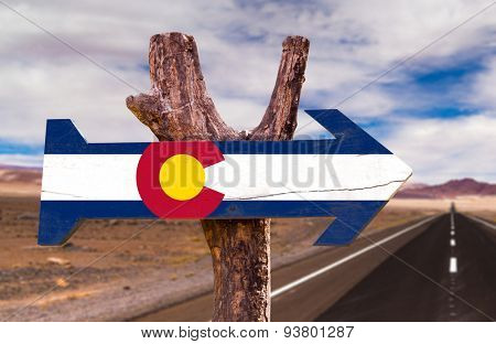 Colorado Flag wooden sign with desert road background