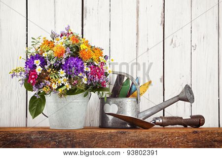 Rustic gardening still-life with flower bouquet in tin bucket, watering can and shovel