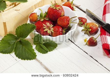 Strawberry fruit in bowl with basket, leaves, blossom, knife and kitchen towel on table