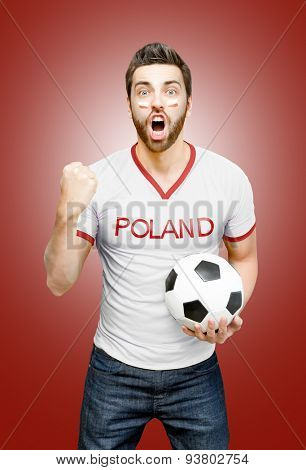 Polish fan holding a soccer ball celebrates on red background