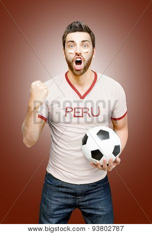 Peruvian fan holding a soccer ball celebrates on red background