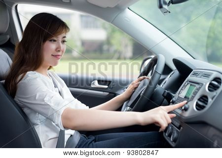 asian female driver touching dashboard in car