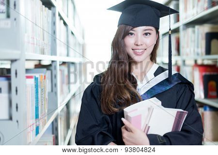 asian female student holding book and wearing academic dress in library