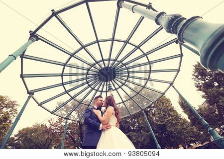 Bride And Groom Hugging Under A Glass Ceiling