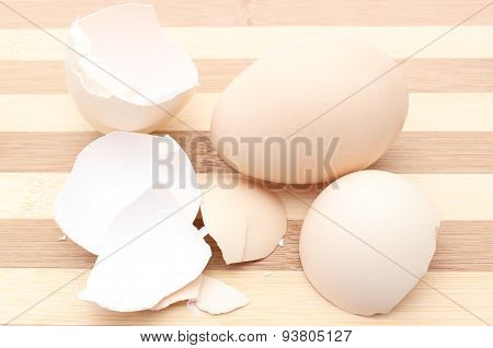 Fresh Egg And Cracked Eggshell On Wooden Background