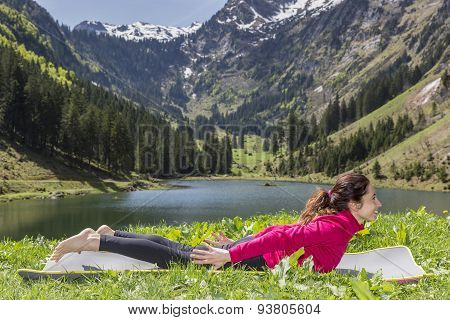 Woman Doing Locust Pose In Yoga Outdoors