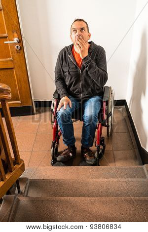man in wheelchair facing a barrier of stairs