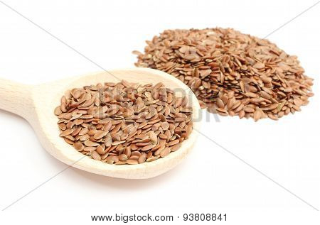 Heap Of Linseed With Wooden Spoon On White Background