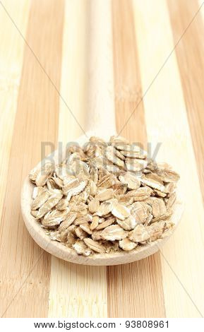 Heap Of Rye Flakes With Wooden Spoon On Cutting Board