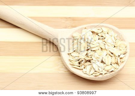 Heap Of Oatmeal With Wooden Spoon On Cutting Board