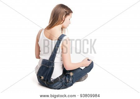 Young woman happily sitting  on the floor drawing in her note pad. Back view