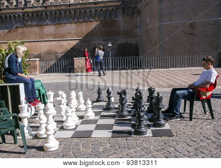Man and woman play a chess near a castel Sant'Angelo
